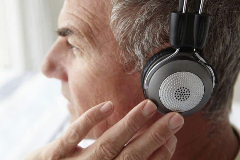 Homem mais velho ouvindo música com fone.