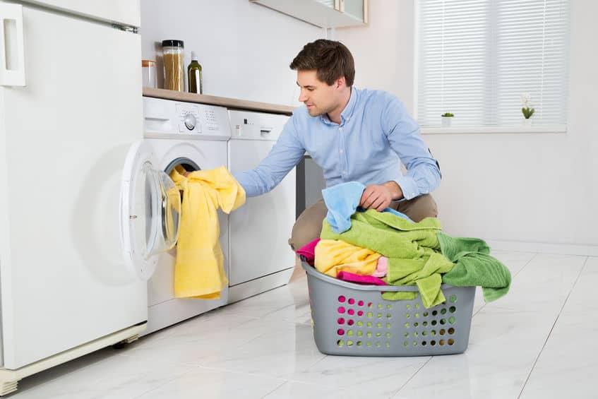 Homem colocando toalhas na máquina de lavar.