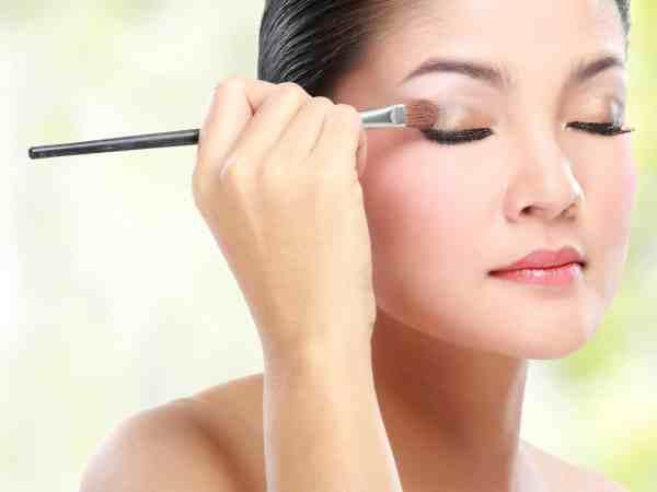 Imagem de mulher fazendo maquiagem.