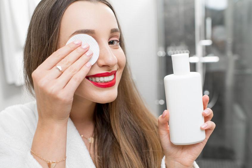 Mulher usa disco de algodão para passar água micelar no rosto ao redor dos olhos