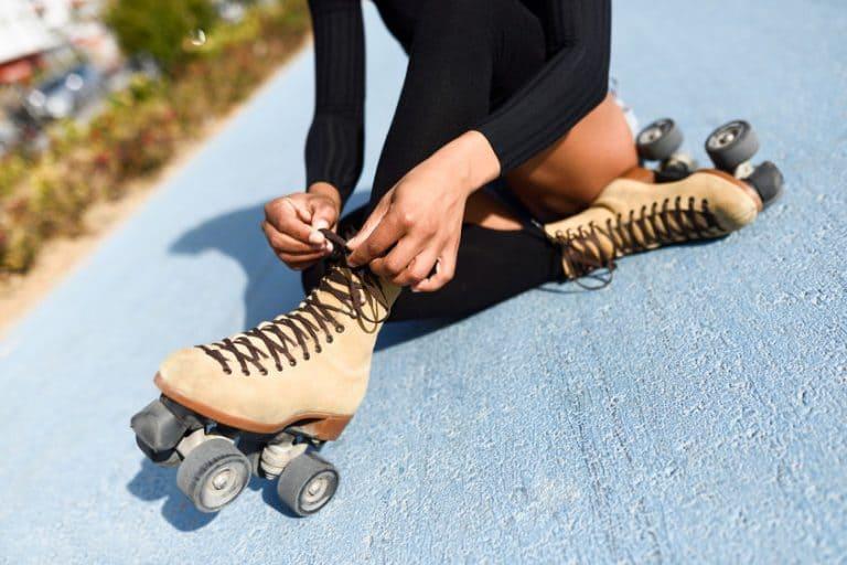 Pessoa sentada utilizando patins marrom.