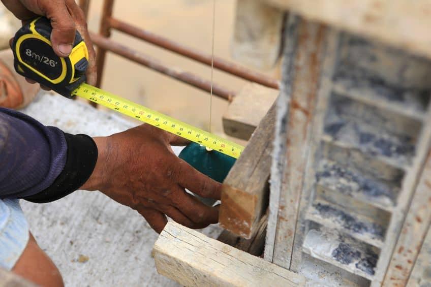 Imagem de pedreiro trabalhando com prumo.