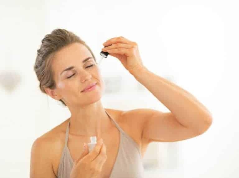 Mulher aplicando óleo no rosto.