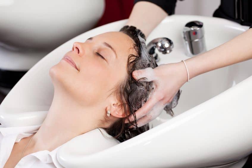 Mulher tendo o cabelo lavado com shampoo no salão