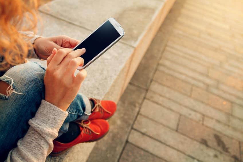 Imagem de mulher mexendo no celular.