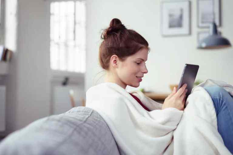Mulher sentada no sofá com um tablet na mão