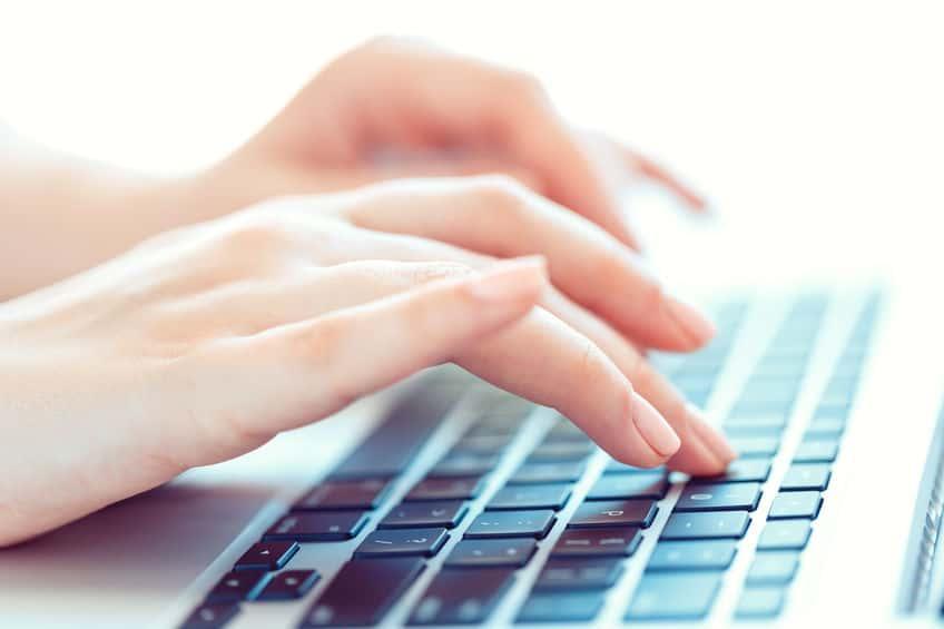 Imagem destaca mãos de mulher digitando em um teclado