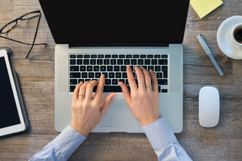 Imagem mostra um teclado integrado ao notebook e mãos digitando