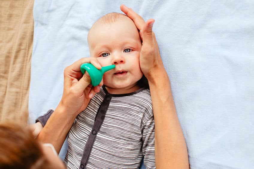 mom with baby and nasal aspirator