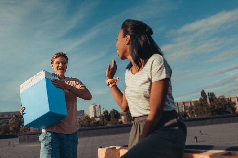 Homem com uma caixa termica ao lado de uma mulher