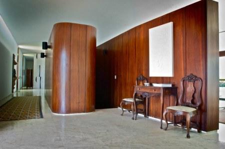 Escada interna e lavabo com paredes divisórias revestidas em painéis de madeira maciça