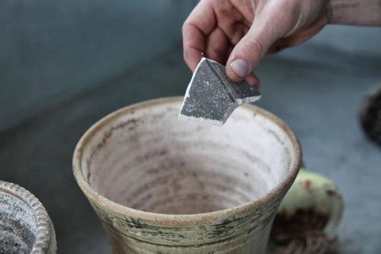pezzetto di vaso rotto, della ghiaia o delle palline di argilla, sul fondo del contenitore per coprire parzialmente il foro di drenaggio