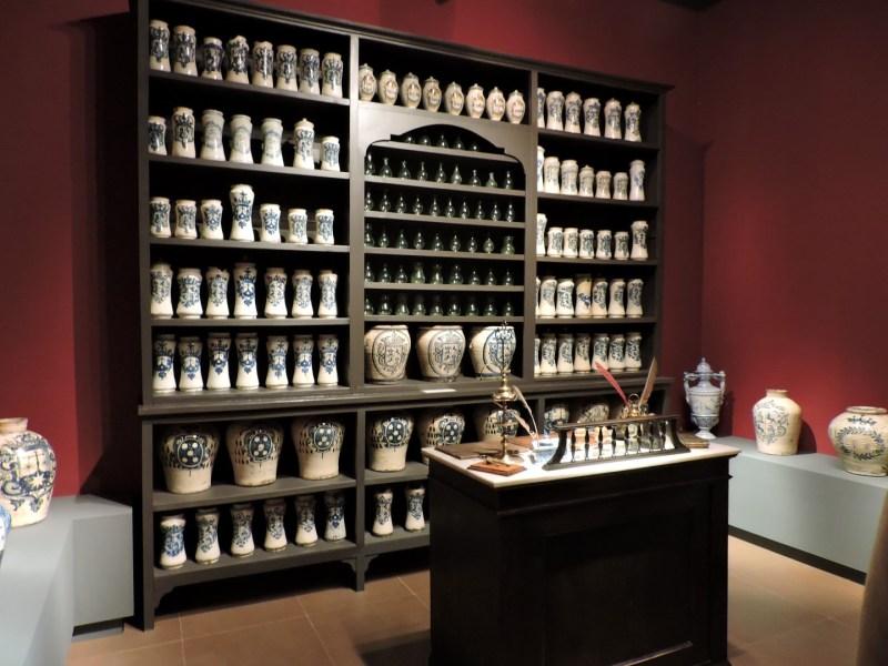 Museo Farmacia Militar - Estantería con albarelos azules y mesa del despacho de farmacia