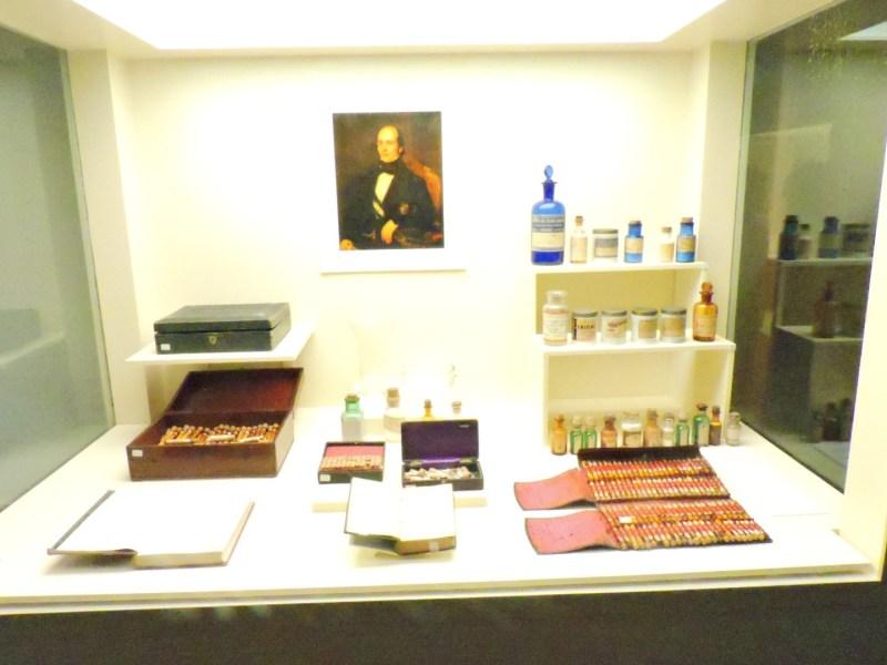 Museo de la Homeopatía - Vitrina con el retrato de D. José Núñez Pernía y diversos maletines y fármacos homeopáticos.