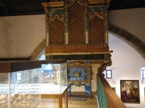 Museo Religioso-Paleontológico - Vitrinas con fósiles a la izquierda, un cuadro religioso a la derecha y, en el centro, el espléndido órgano de la iglesia.