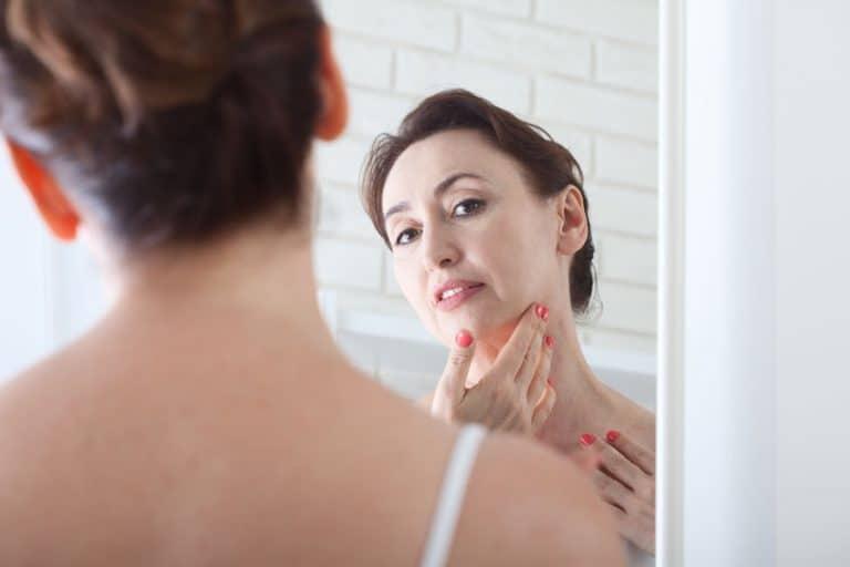 Mujer de edad media mirandóse al espejo