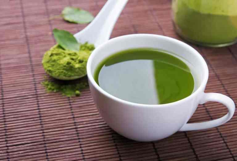 Taza de té verde junto a cuchara con té en polvo