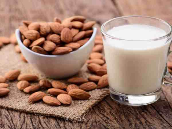 Almond milk in glass with almonds