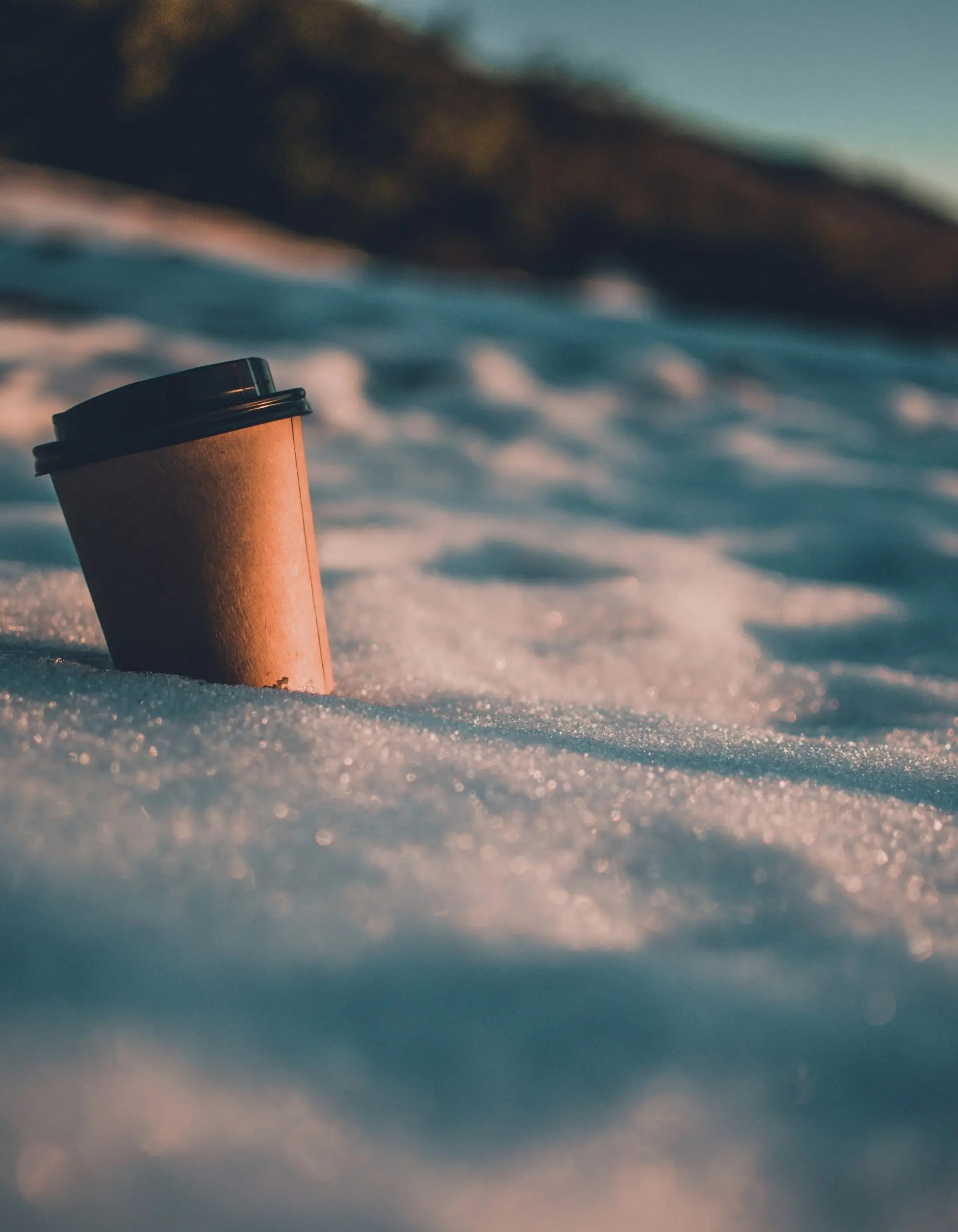 brown and black coffee cup on snow covered ground