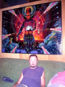 "Ingo Swann sitting in front of his painting ""Lightbearer."""