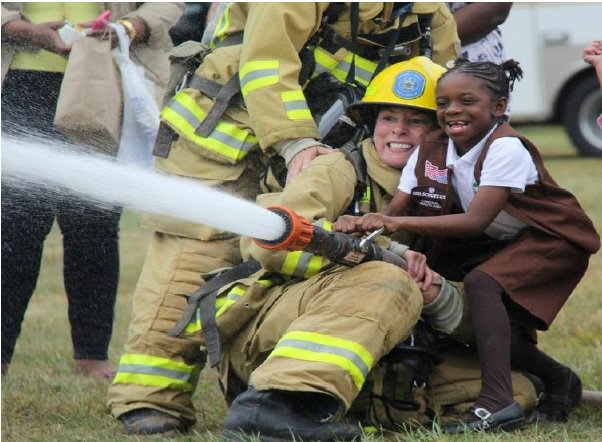 A possible future firefighter learns the basics of handling a fire hose, while also experiencing the thrill of managing the power of water.