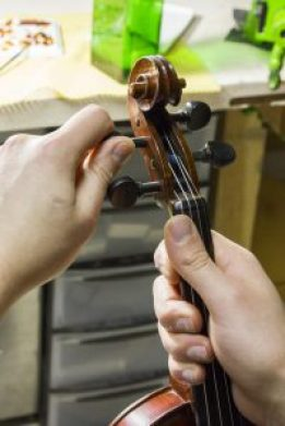 La meilleur position pour accorder son violon : être assis, le poser sur ses jambes et tourner les chevilles en tenant fermement l'instrument.