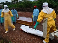 Medicins Sans Frontieres (MSF) medical workers wearing protective clothing carry the body bag of an Ebola victim at the MSF facility in Kailahun, on August 14, 2014. Kailahun along with Kenama district is at the epicentre of the world's worst Ebola outbreak. The World Health Organisation (WHO) revealed that the latest death toll from the Ebola virus in Guinea, Sierra Leone, Liberia and Nigeria had claimed more than1000  lives. Health Organisations are looking into the possible use of experimental drugs to combat the latest outbreak in West Africa. AFP PHOTO / CARL DE SOUZA