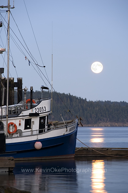 The fishing boat Northern Ocean at the dock in Hope Bay with the full moon rising over Mayne Island, Hope Bay, North Pender Island, British ColumbiaNorthern Ocean at the dock in Hope Bay