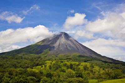 Volcano Arenal in Costa Rica on a partly cloudy day. Northeastern slopes.Arenal Volcano is an active andesitic (meaning that the rock has been crystallized from silicate minerals) stratovolcano in north-western Costa Rica, where Arenal is the youngest and most active of all the mountains. It was presumed extinct until July 29, 1968 when an earthquake caused it to erupt, after approximately 400 years of dormancy. Arenal rises 1657 m above sea level and overlooks Lake Arenal; both are part of Arenal Volcano National Park