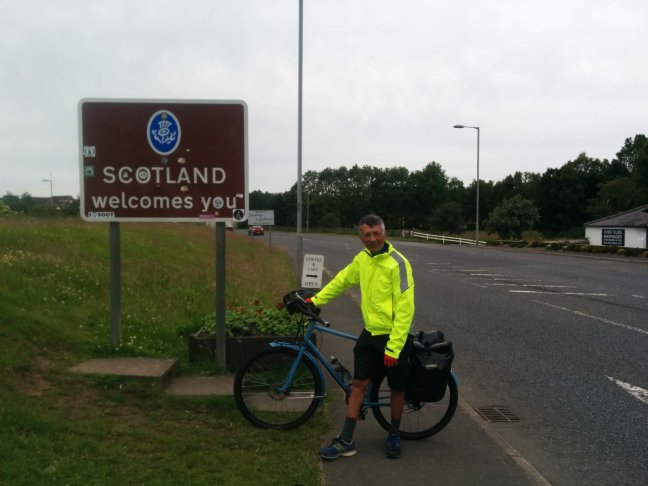 Cyclist standing by Welcome to Scotland sign