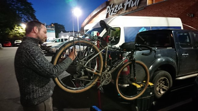 Mechanic fixing bike in dark parking lot