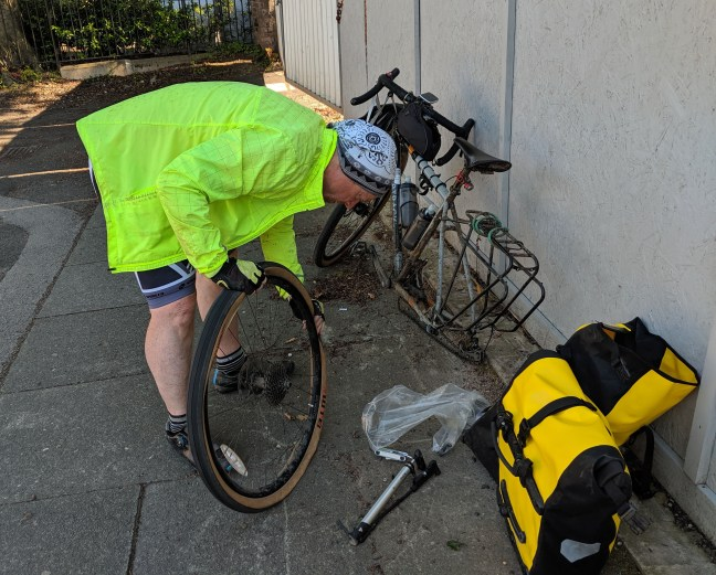 Cyclist in yellow windbreaker fixing a flat tire