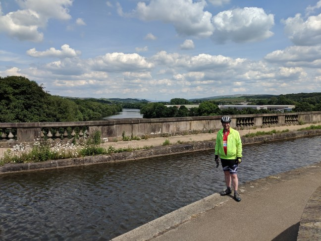 Cyclist standing next to canal on a bridge over a river
