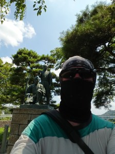 Masked cyclist in front of statue of Tamagawa Brothers