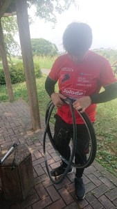Cyclist inserting innertube into bicycle wheel
