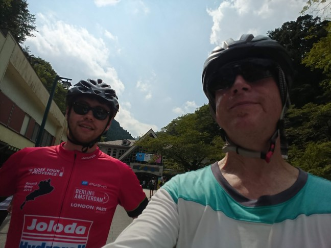Two cyclists pose in front of the entrance to the Takaosan cable car and lift