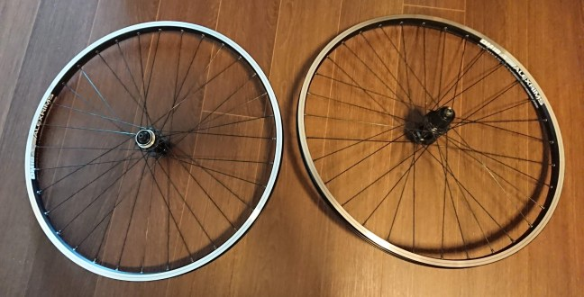 Two bicycle wheels on a wooden floor