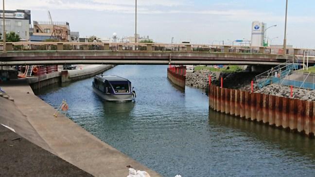 Tourist boat passing under bridge