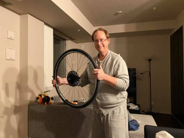 Man holding a rear bicycle wheel and making a thumbs-up gesture