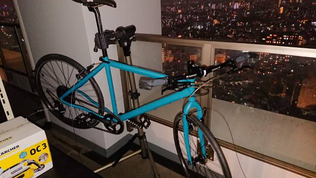 Bicycle in workstand overlooking darkened cityscape