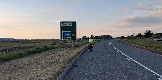 Cyclist passing a road sign at Shap Fell Summit