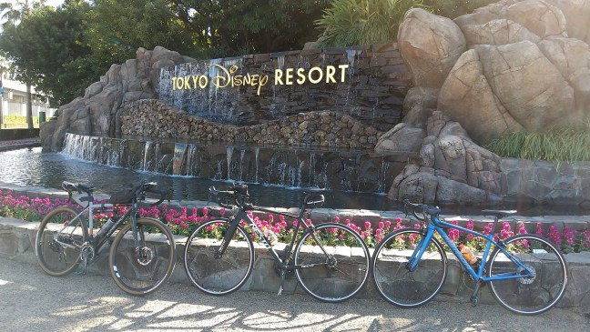 Three cycles leaning against flowerbed at Tokyo Disney Resort