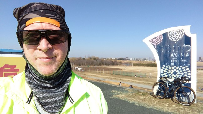 Selfie of biker in front of Arakawa river marker with bicycle