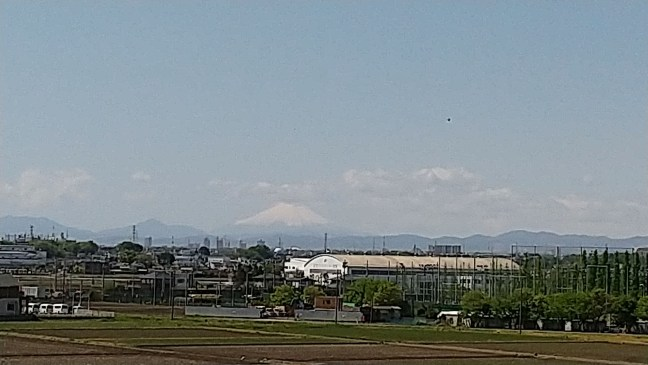 Fujisan in partly cloudy skies, with farmland and factories in the foreground