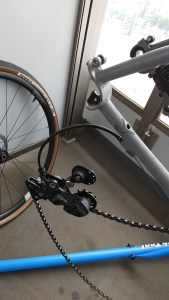 Detail of bicycle rear derailleur and modular drop-out separated from frame