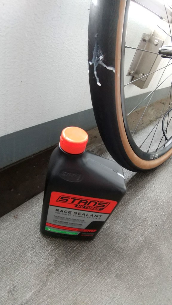 Detail of bicycle tire showing sealant leaking from hole, and sealant bottle