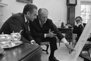 President Gerald R. Ford and the Shah of Iran confer over a map during the Shah's May 1975 visit to Washington, D.C. Secretary of State Henry Kissinger sits in the background. (Photo courtesy of Gerald R. Ford Presidential Library)