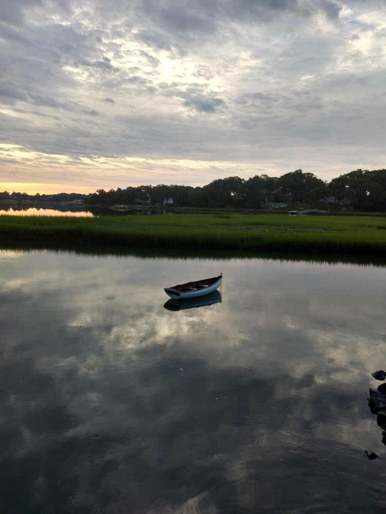 Image of a blue rowboat, alone in a harbor, with the sky above reflected in the still harbor below.