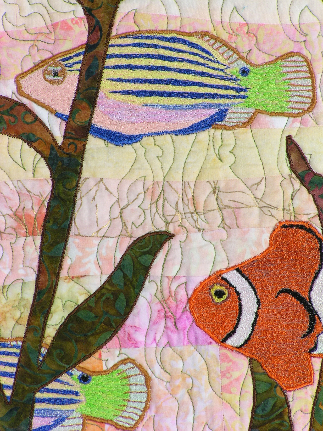 Closeup shows the thread painted clownfish, as well as how the background quilting motif reflects the outline of seaweed.