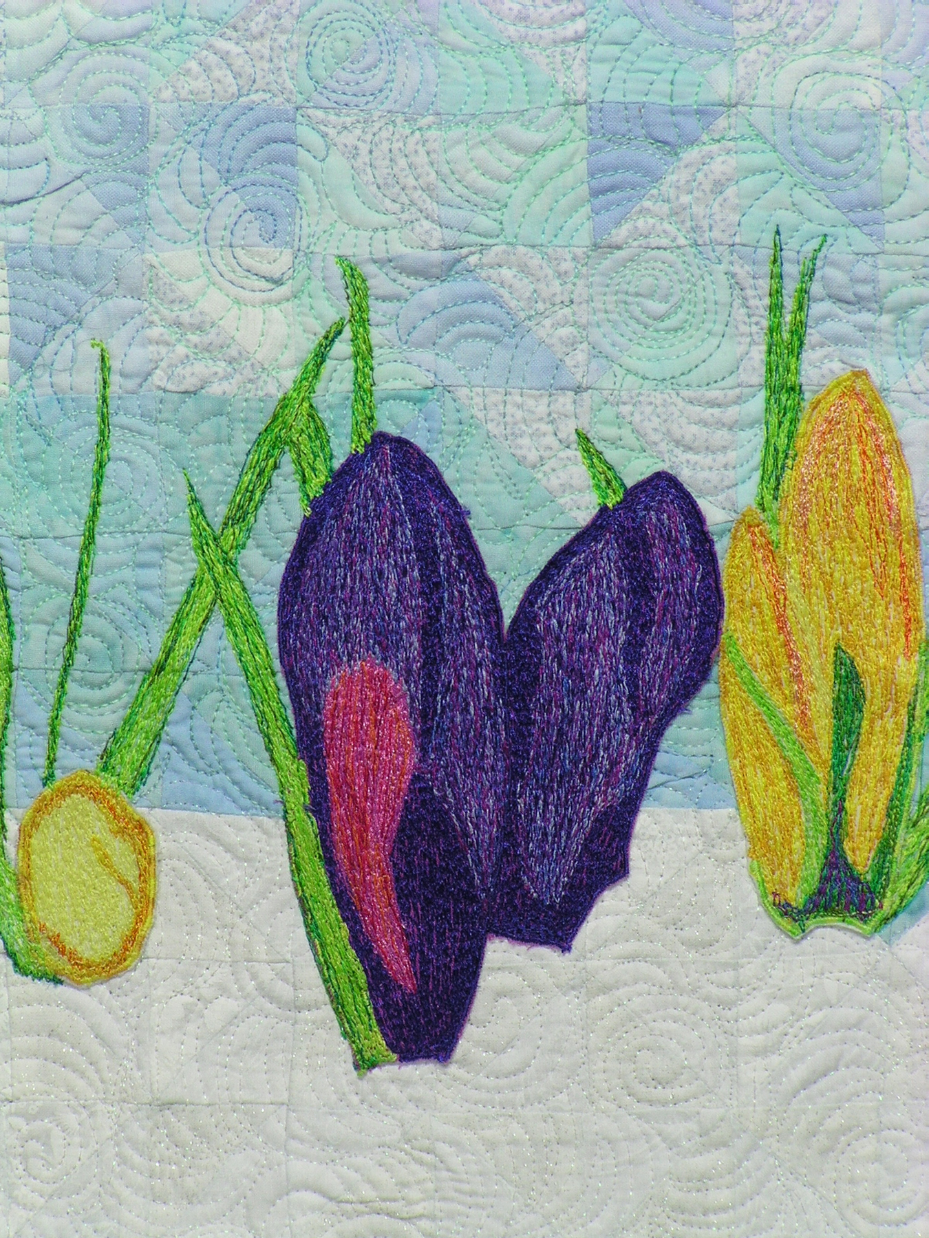 This closeup depicts the deep purple thread painted crocus flanked by a barely there yellow crocus on the left and fully budded but not bloomed one on the right.
